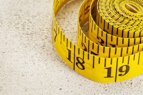 yellow inch tape measure, rolled up