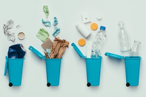 A flat lay of four blue trash cans laying on a white background with recycled items.
