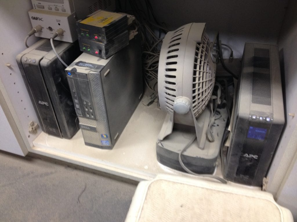 electronic equipment beneath workstation covered in dust